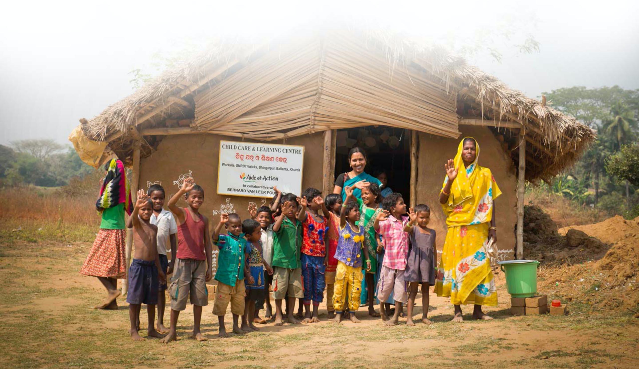 Un groupe d'enfants posant avec leur maîtresse devant leur école